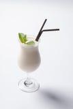 Milkshake délicieux avec une feuille de menthe sur le dessus sur un fond blanc Photographie stock libre de droits
