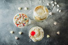 Milkshake drinks with whipped cream and marshmallows. Top view royalty free stock image