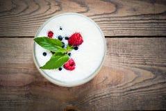 Milkshake in a glass jar. Milkshake with raspberries, blueberries and banana in a glass jar at wooden table Stock Images