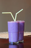 Milkshake Glasses. A view of two glasses with straws containing blue colored milkshake Stock Photos
