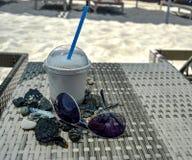 Milkshake i en plast- kopp på en tabell med exponeringsglas och kiselstenar royaltyfri foto