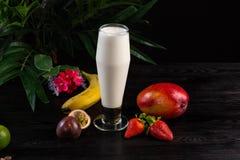 Milkshake i ett h?gv?xt exponeringsglas och frukter p? en m?rk bakgrund arkivfoton