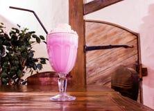 Milkshake i ett stort härligt exponeringsglas med ett sugrör på en trätabell arkivfoto