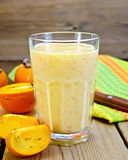 Milkshake with persimmons in glass on board Stock Images