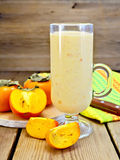 Milkshake with persimmons in goblet on board Stock Photos