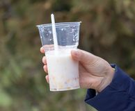 Milkshake in a plastic cup in hand.  stock images