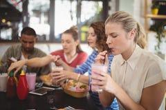 Milkshake potable de jeune femme avec des amis au café Images libres de droits