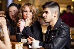 Milkshake potable de jeune femme tout en se reposant avec des amis au café Photos libres de droits
