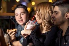 Milkshake potable de jeune femme tout en se reposant avec des amis au café Image stock