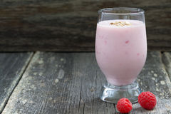 Milkshake with raspberries on a wooden background, close-up. Horizontal Royalty Free Stock Photos