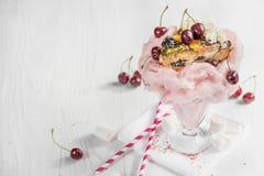 Milkshake rose très grand avec les cerises et le chocolat avec un tarte Image stock