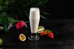 Milkshake in a tall glass and fruits on a dark background royalty free stock photos