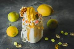 Milkshake with whipped cream, dripping sauce and yellow macaroon stock photos