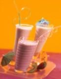 Milkshakes με τα άχυρα κατανάλωσης στο δίσκο στο κίτρινο υπόβαθρο Στοκ Φωτογραφία