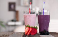Milkshakes που γίνεται με τα φρέσκες βακκίνια και τις φράουλες σε ένα γυαλί στοκ εικόνα με δικαίωμα ελεύθερης χρήσης