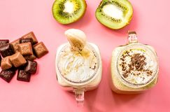 2 milkshakes банана и кивиа в опарниках каменщика при обломоки creme и шоколада на верхнем украшенные с кивиами и scatter шоколад стоковое изображение