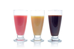Milkshakes. A three milkshakes with flavors of strawberry, vanilla and chocolate reflected on white background stock photo