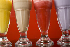 Milkshakes Close-Up. Four vividly colored milkshakes in a cool cafe - Mango, Chocolate, Raspberry and Blueberry Stock Photography