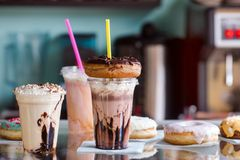Milkshakes with donuts for takeaway in a cafe. Delicious milkshakes with donuts plastic cups for takeaway in a cafe royalty free stock image