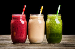Milkshakes and smoothies. Three milkshakes and smoothies on wooden table stock photo