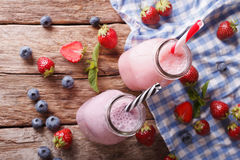 Milkshakes with strawberries and blueberries in bottles close-up Stock Photos