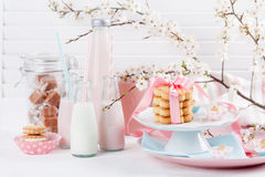 Milkshakes and sweets in pink and blue. Four bottles of milkshakes, three with straws and glass of milk and plates with cookies and biscuits tied with pink stock images