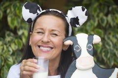 Αστεία ώριμη γυναίκα με το milksop και την αγελάδα Στοκ Φωτογραφίες