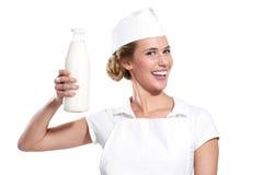 Milkwoman feliz novo que mostra uma garrafa do leite fresco Fotografia de Stock