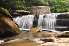 Milky Blue Ridge Waterfall Nature Landscape. A long exposure Appalachian waterfall landscape with forest and large rocks. Golden tones in the river and green Stock Image