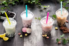Milky bubble tea with tapioca pearls in plastic cup.  royalty free stock images