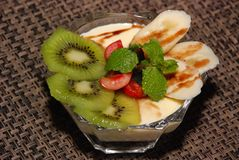 Milky desert with kiwi, cherry, banana, mint and chocolate toping royalty free stock image