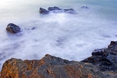 Milky early morning seas and rocks in Spain Stock Image