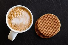 Milky frothy coffee in white mug next to a couple of round waffl Stock Photos