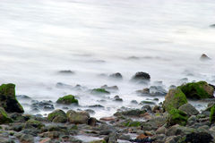 Milky sea. The sea gently laps at the stones on the beach. A long exposure has created the milky sea effect Stock Images