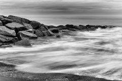 Milky sea splashing over rocks Stock Images