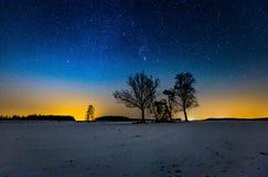 Milky sposób i gwiaździsty niebo nad zimy wioską krajobrazową i odległą fotografia royalty free
