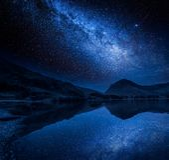 Milky sposobu i gwiazd odbicie w jeziorze, Gromadzki jezioro, Anglia Zdjęcie Royalty Free