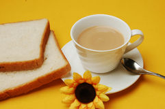 Milky tea with bread. A cup of milky tea with bread and spoon royalty free stock image