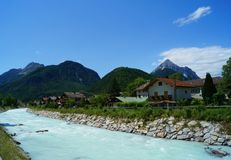 Milky turquoise mountain river running trough the village Mittenwald. Milky white turquoise turbulent mountain river channelled through the German city royalty free stock images