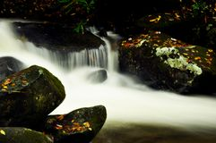 Milky waters flow from a small stream. Royalty Free Stock Images