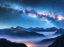 Milky Way above mountains in fog at night in summer. Landscape with alpine mountain valley, low clouds, purple starry sky with milky way, city illumination royalty free stock photo