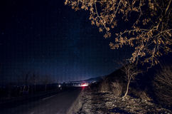 Milky Way above a road and tree close up with car lights on brenches. Night road with stars on sky, Sheki, Azerbaijan Stock Image