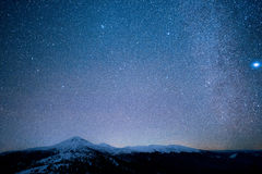 Milky Way above the snowy peaks of the Mountains Royalty Free Stock Photo