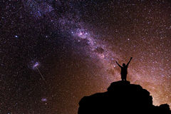 Milky Way. Beautiful night sky with stars and silhouette of a standing alone man on the mountain. Stock Image