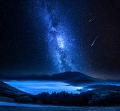 Milky way and falling stars over mountains, Castelluccio, Umbria, Italy royalty free stock image