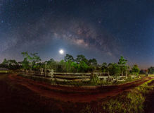 Milky way and fullmoon over dirt road in country side Stock Image