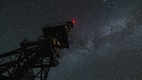 Milky way galaxy over communication tower in starry night sky Time lapse Zoom. Milky way galaxy circling over communication tower in starry night sky. Astronomy stock video footage