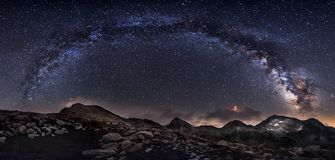 Milky Way galaxy and mountain peaks panorama.