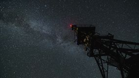 Milky way galaxy moving over communication tower in starry night Time lapse. Milky way galaxy moving over communication tower in starry night sky. Astronomy Time stock video