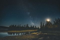 Milky Way galaxy night sky over forest with moon and reflection. Vancouver Island, Tofino, Canada royalty free stock photo